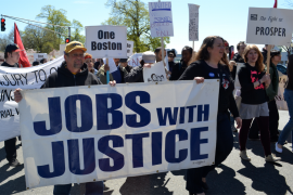 People marching while holding Jobs With Justice banners